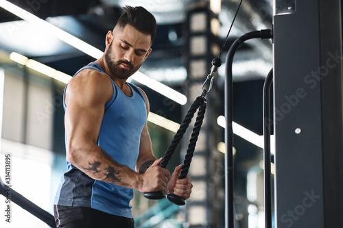 Fototapeta premium Muskularny mężczyzna ćwiczy z aparatem treningowym w siłowni
