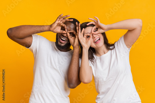 Cheerful interracial couple making funny glasses with fingers, fooling together Fototapet