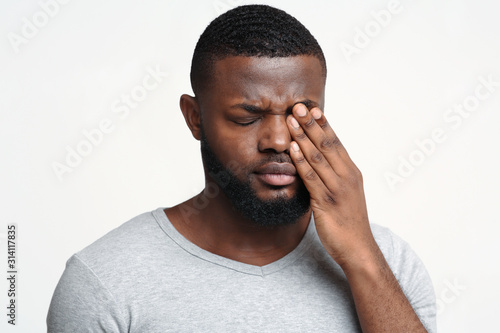 Fotografiet Sad black guy touching his eye, suffering from conjuctivitis