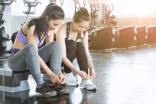 Photographie  Young women tying shoelaces of sneaker on a floor at indoor gym with machine and elliptical background prepare to exercise workout