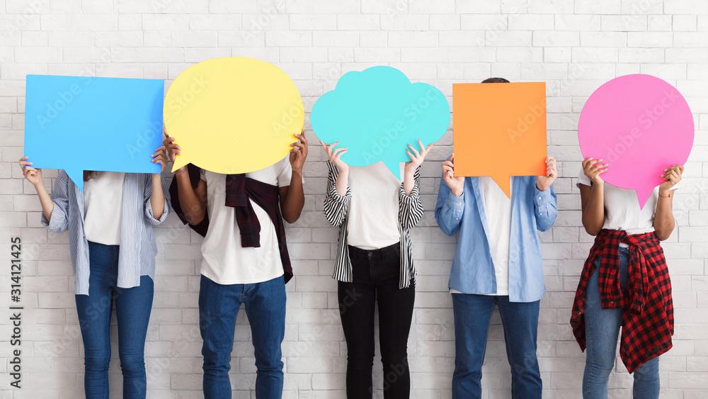 Fototapeta Everyone has own opinion. Teens holding empty speech bubbles