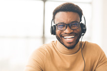Happy Consultant With Headset Looking At Camera
