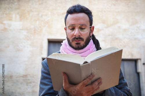 Obraz Bearded young man wearing vintage clothes reading a book. Outdoors shooting. Culture concept - fototapety do salonu