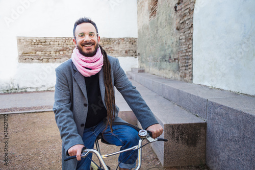 Obraz Bohemian man smiling on a bicycle. Eco-friendly mobility concept - fototapety do salonu