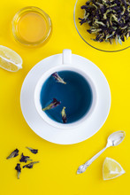 Blue Flower Tea In The White Cup In The Center Of  The Yellow  Background. Top View. Location Vertical.