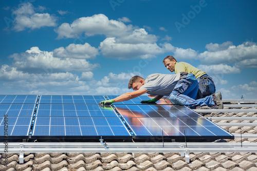 Obraz Installing solar photovoltaic panel system. Solar panel technician installing solar panels on roof. Alternative energy ecological concept. - fototapety do salonu