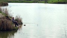 Patient Fisherman Sits By The Lake Waiting For Bites. Fishing. Cloudy Autumn Day