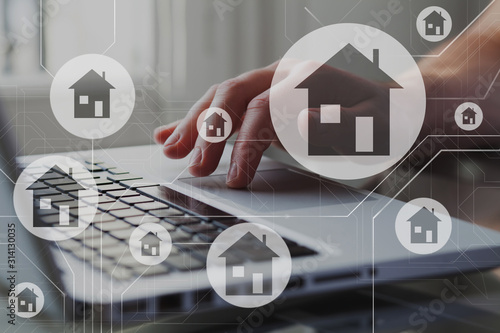 Real estate concept. Houses on schema diagram. Person search, compare and select proper rent apartment in laptop.
