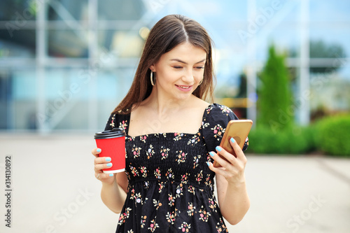 Photo  A young woman reads social networks and drinks coffee