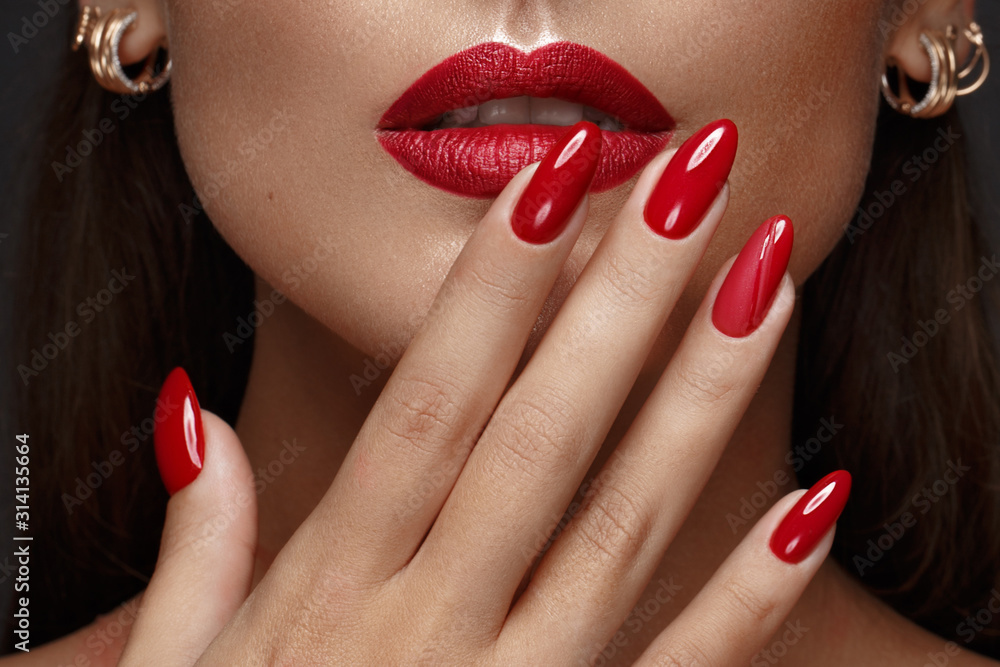 Fototapeta Beautiful girl with a classic make-up and red nails. Manicure design. Beauty face.