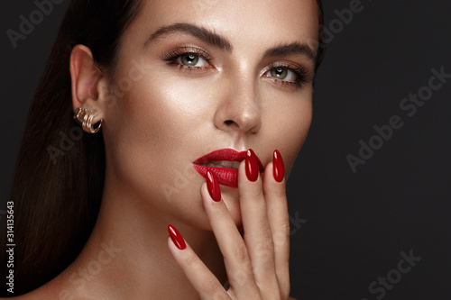 Obraz na plátně Beautiful girl with a classic make-up and red nails