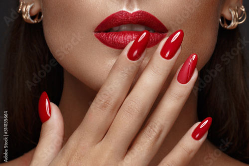 Obraz Beautiful girl with a classic make-up and red nails. Manicure design. Beauty face. - fototapety do salonu
