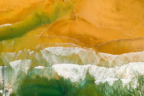 Top down view of beautiful beach with ocean waves crashing and foaming