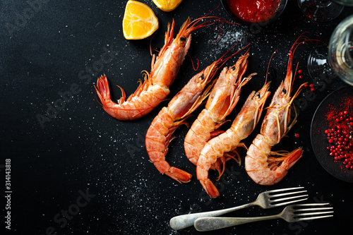 Fotomural Uncooked giant shrimps on dark table