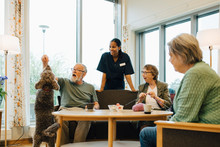 Women Looking At Man Playing With Dog At Retirement Home