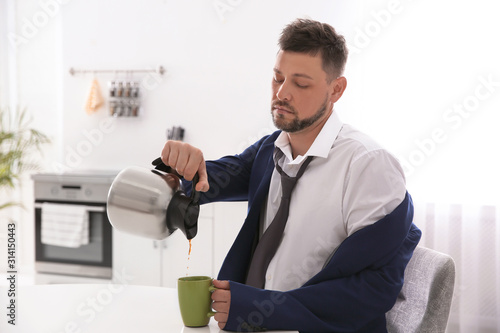 Fototapeta Sleepy man pouring coffee into cup at home in morning