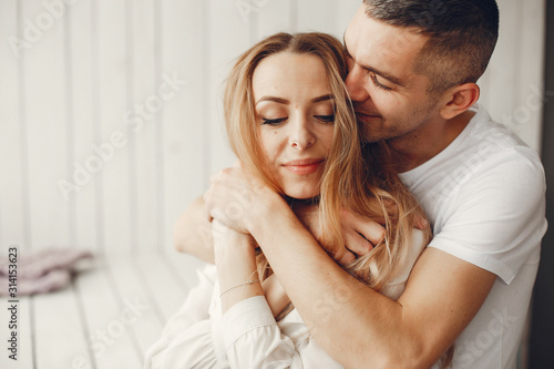 Obraz Couple sitting at home. Beautiful blonde with her husband. Man in a white shirt - fototapety do salonu