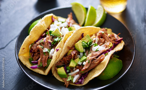 plate of mexican carnita tacos with beer in background - 314153656