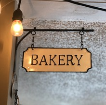 Close View Of Metal Bakery Sign Hanging On A Building Exterior