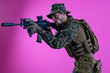 canvas print picture - soldier in action aiming laseer sight optics pink background
