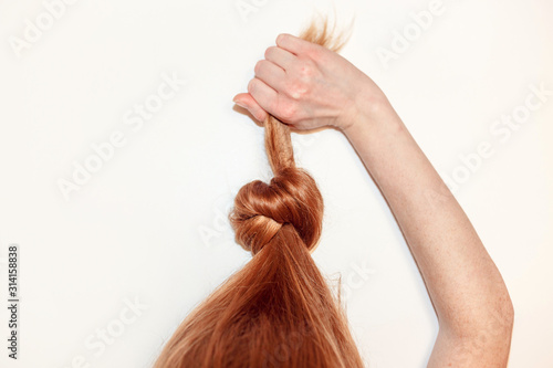 Red-haired girl pulls herself up in a knotted hair Wallpaper Mural