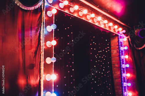 Foto Light Bulbs On Stage Theatrical scene with colored glitter neon bulbs for presentation or concert performance