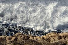 Aerial View Of Ocean Tide Coming Into Rocks.
