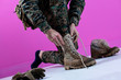 canvas print picture - soldier tying the laces on his boots