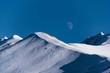 canvas print picture - Winterlandschaft in den Bergen vor blauem Himmel mit Mond