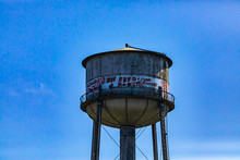Architectural Details Of An Old Water Storage Tank Tower. Weathered In A State Of Disrepair, Covered In Graffiti. Against A Blue Sky With Copy Space
