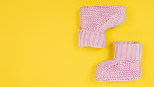 Pink Cute Booties For Newborn Baby. Baby Girl Shoes On Yellow Background. Banner 16x9, Copy Space.