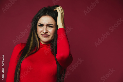 Beautiful brunette baffled caucasian girl dressed in red pullover is scraping he Canvas Print