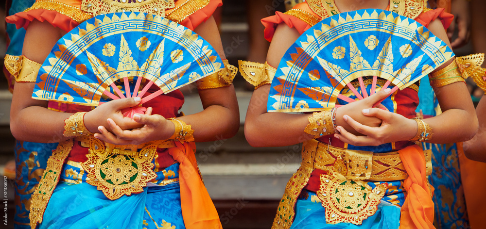 Fototapeta Asian travel background. Group of beautiful Balinese dancer women in traditional Sarong costumes with fans in hands dancing Legong dance. Arts, culture of Indonesian people, Bali island festivals.