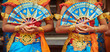 Leinwanddruck Bild - Asian travel background. Group of beautiful Balinese dancer women in traditional Sarong costumes with fans in hands dancing Legong dance. Arts, culture of Indonesian people, Bali island festivals.