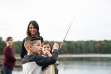 Young Boy Fishing With His Fam...