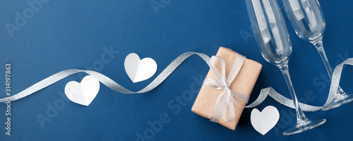 Fototapeta wineglasses and gift box on classic blue background. Background for holiday, birthday, wedding, Valentine's day, Women's Day party. Top view, flat lay banner. Copy space obraz na płótnie