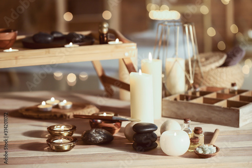 Obraz Glowing candles with spa supplies on table - fototapety do salonu