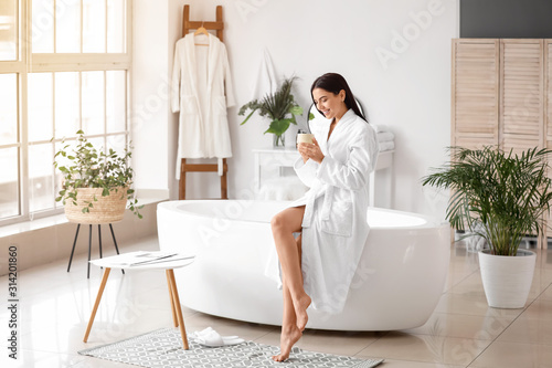 Fotografie, Tablou Beautiful young woman drinking coffee in bathroom