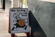 Now Serving Personal Pizza Signboard In Front Of Pizza Parlor Restaurant On Sidewalk