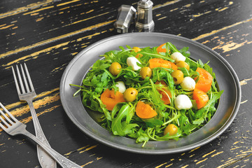 Plate with tasty salad on wooden background