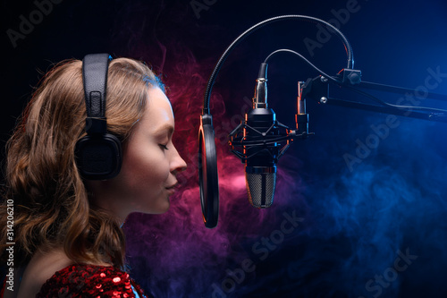 Fotografie, Obraz Vocal teacher singing with a studio microphone in a studio with a bright background
