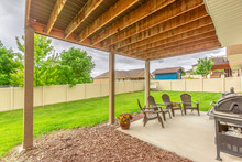 Patio At The Backyard Of A Home With Roof Columns Chairs And Barbecue Grill