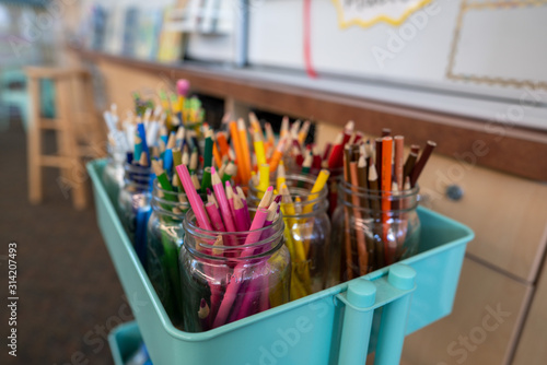 Cart filled with jars of color pencils for artwork in classroom