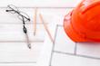 Builder helmet and blueprints on white wooden background