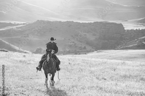 black and white horseback riding in mountains
