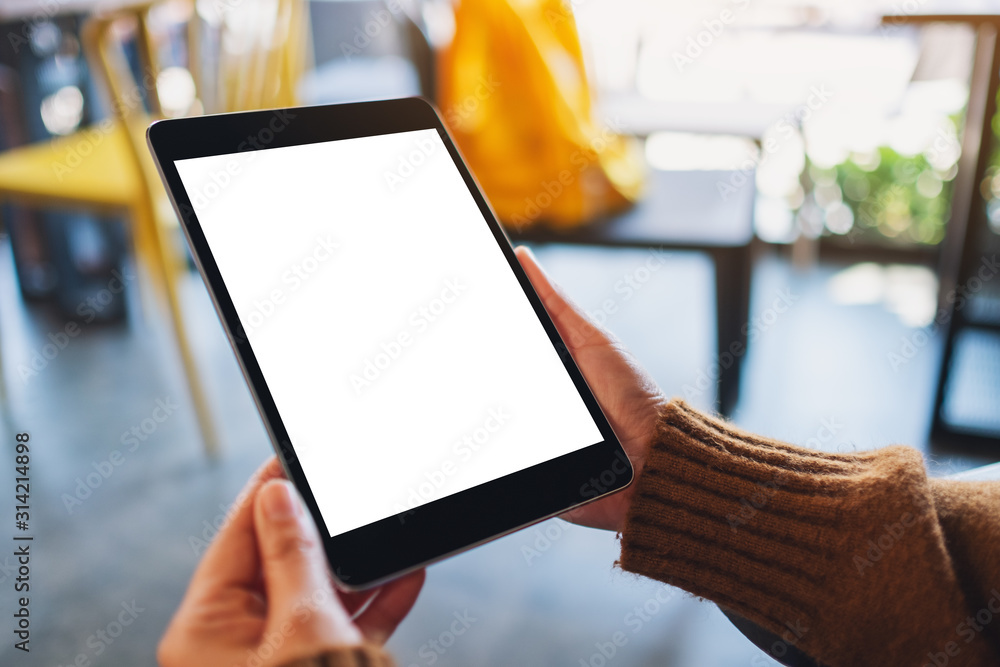 Fototapeta Mockup image of a woman sitting and holding black tablet pc with blank white desktop screen