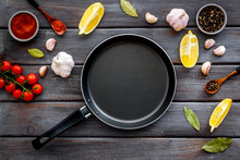 Cooking Mockup. Frying Pan Among Spices And Vegetables On Dark Wooden Desk Top-down Copy Space