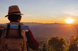 male tourist with backpacks stand to the top of mountain and enjoying sunset.