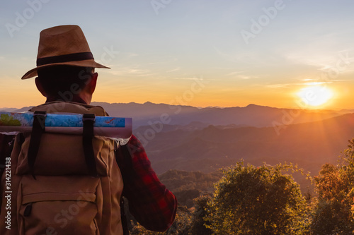 Obraz male tourist with backpacks stand to the top of mountain and enjoying sunset. - fototapety do salonu