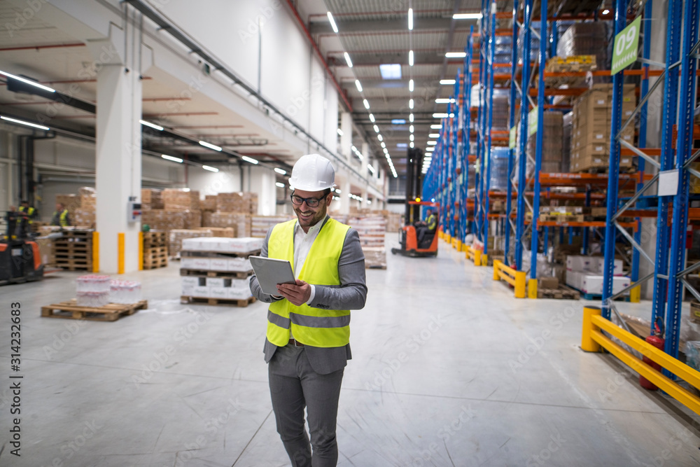 Fototapeta Warehouse manager walking through large storage area and holding tablet while forklift operating in background.